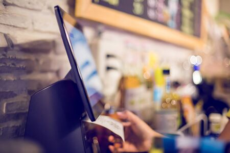 Blurry picture of cashier is printing receipt with cash register machine in cafe or store. Saleswoman receiving payment from customer in cafe or store. Blurry image for business background.