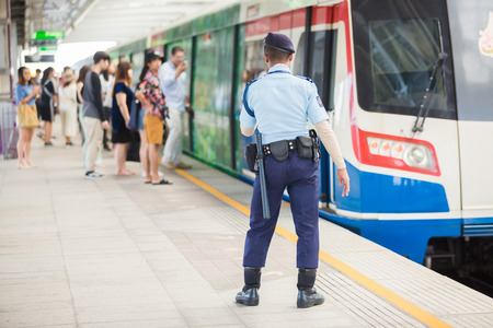 Bangkok Thailand : October 17, 2019 : A security guard standing and watch to safety with blurry passengers going up and down from the BTS Skytrain.