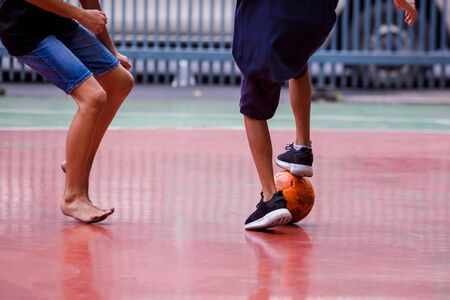 Futsal players between barefoot and sport shoes. Soccer players fighting each other by kicking the ball. Indoor soccer sports hall. Concept of inequality.