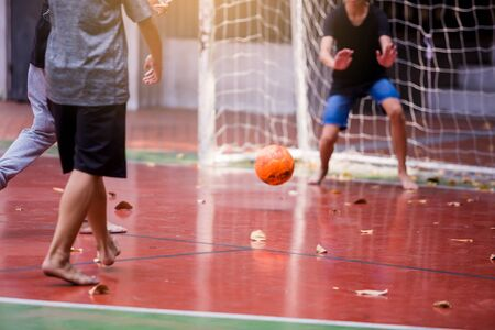 Futsal players barefoot. Futsal player control and shoot ball to goal with goalkeeper. Soccer players fighting each other by kicking the ball. Orange ball, Futsal floor.
