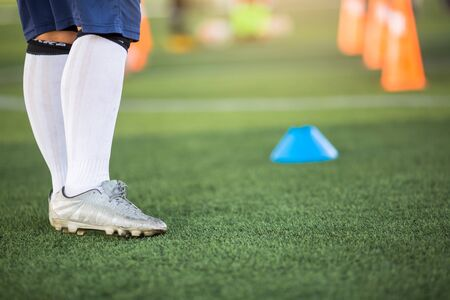 Young boy soccer player is standing with blurry marker cones on green artificial turf. It is activity on holiday. Football training in academy.
