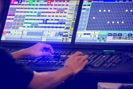 Technicians are controlling the sound system and lighting system on the concert stage. The sound engineer is controlling the system at the control panel. Standard-Bild - 138456921