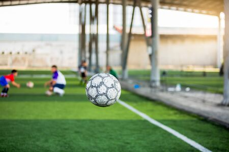 Soccer ball bounce with blurry green background and soccer training on artificial turf. 写真素材