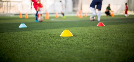 Marker Cone on green artificial turf with blurry kid soccer players are training background. Soccer academy.