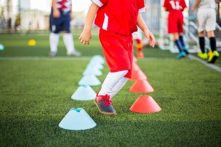 Giocatore di calcio per bambini che fa jogging e salta tra indicatori di cono rosso e blu su erba artificiale verde per l'allenamento di calcio. Accademia di calcio o di calcio.