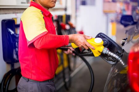 Yellow oil nozzle in gas station. Hands refilling the car with fuel at the gas  station, black car in gas station, refilling the car with fuel at the refuel station, the concept of fuel energy. Stock Photo