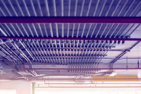 Blurry picture of electrical conduit and cabling. Blurry image for construction background. The rows of electrical conduit and signal cables in the parking building.
