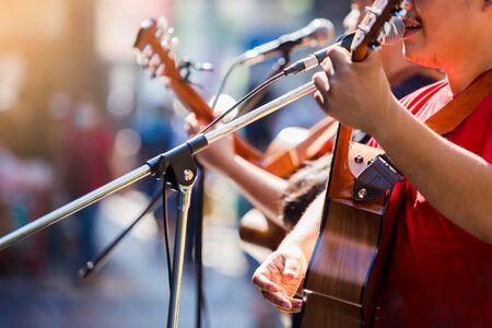 Enfoque selectivo a las manos del músico tocando la guitarra en un espectáculo en vivo en el escenario, el concepto de instrumento musical. Foto de archivo