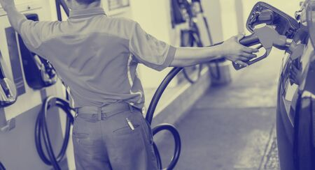 Selective focus to hands refilling the car with fuel and press control panel at the gas  station, refilling the car with fuel at the refuel station, the concept of fuel energy. Stock Photo