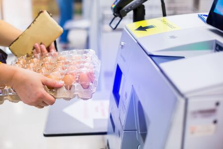 Selective focus to the woman is scanning the product (eggs) at the automatic payment machine. self service machine in modern supermarket, self-service paypoint tills in supermarket, Bangkok Thailand.