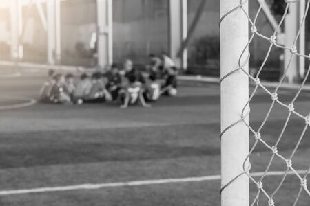 Black and white soccer background image. Mesh goal with blurry young boy soccer players sitting with coach on  artificial turf. 写真素材