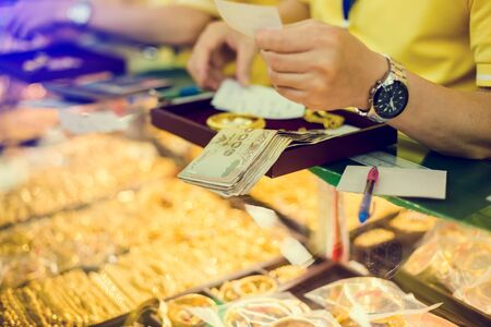 selective focus to staff are counting banknote, customers are buying gold jewelry in the gold shop at Yaowarat, Bangkok, Thailand.