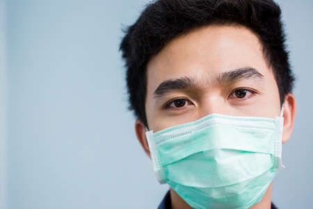 Asian man wears a face mask that protects against the spread of coronavirus disease. Close- up of a young woman with a surgical mask on her face against Covid-19.