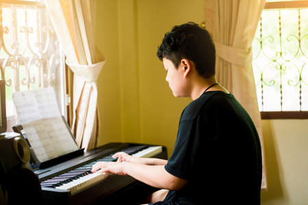 Selective focus to Asian boy is playing piano in home. Musical instrument for learning music. The music learning and enjoy concept.