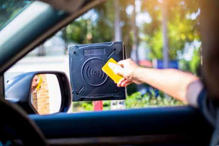 Selective focus to RFID reader with blur driver use key card to open the door for safety. Driver hold card to scan at RFID card reader station for open the car park door. Security system for parking.