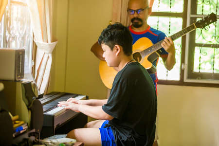 Selective focus to Asian boy is playing piano with blurry father playing guitar in home. Musical instrument for learning music. The music learning and enjoy concept.