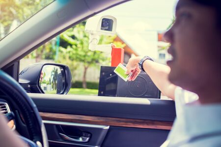 Man driver stop car and use key card to open the door for safety with blurry CCTV camera. Driver hold card to scan at RFID card reader station for open the car park door. security system for parking.