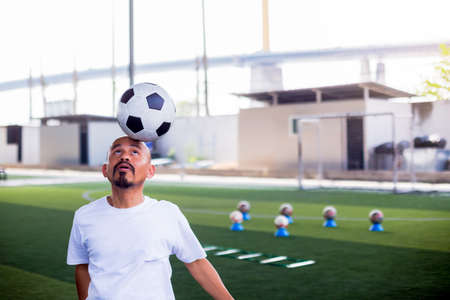 Selective focus to ball on head of football coach to demo for football player with blurry marker cones and soccer equipment. Footballer is train to balancing a ball on his head. 版權商用圖片