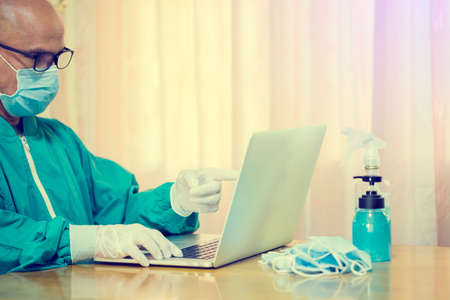 Selective focus to hand of Medical doctor or Psychologist is wearing mask and working with laptop in the laboratory.