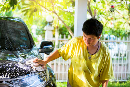 Selective focus to Asian boy washing black car with cloth sponge and shampoo at home. The concept of clean the car at home by yourself. 版權商用圖片