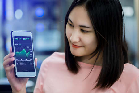 Asian beautiful woman holding and showing blur smartphone with green stock graph and smiley face in office. The concept of the Asia economy is improving.