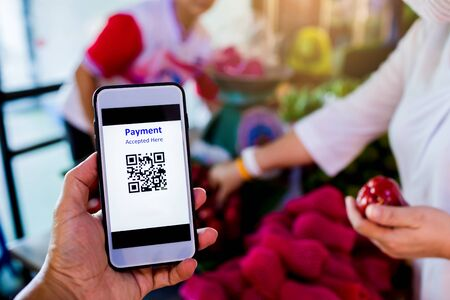 Scanning QR code payment with blurry staff and customer buying fruit in market accepted generate digital pay without money. E wallet and cashless technology concept. Stock Photo