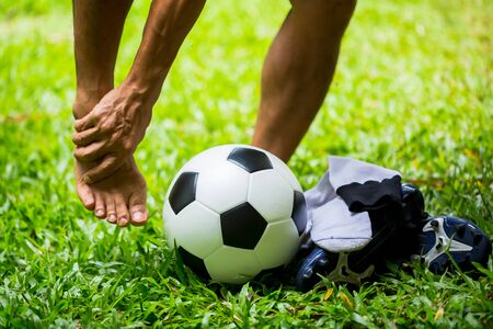 Soccer ball and sport shoes on green grass with soccer player catch the ankle of the feet because of pain. Soccer player was injured in the foot with pain during competition or practice. Banque d'images
