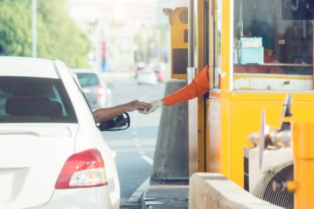 Selective focus to driver pay for the expressway. Man pays money to a cashier for a toll road toll gate motorway entrance. Hand paying express toll way on the road. pay express way. Stock Photo