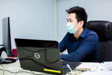 Businessman working with laptop. He wearing a mask in office.