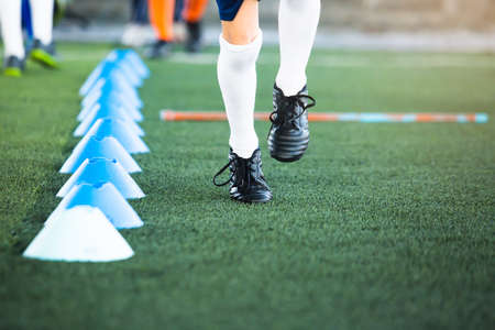Selective focus to kid soccer players jogging beside cone marker  on green artificial turf for training. Football or soccer academy.