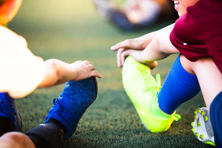 Selective focus to soccer players are stretching their hands to catch their feet to warming up and stretching the body and foot before the competition or practicing. Stock Photo