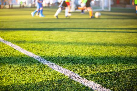 Selective focus to white lines on green artificial grass football fields with kid soccer player. Football or soccer academy. Stock Photo
