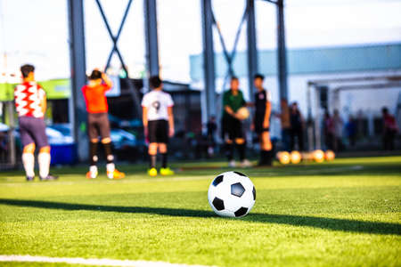 Selective focus to soccer ball on green artificial turf with blurry soccer team is training. Sport background. Soccer background.