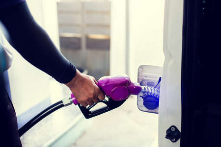 hand refilling the car with fuel at the gas station, car in gas station, refilling the car with fuel at the refuel station, the concept of fuel energy.