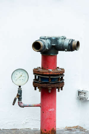 Old red fire hydrant in street with pressure gauge mounted on white background.