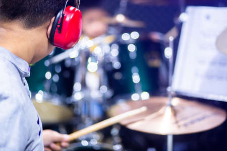 Selective to red ear muffs over head of musicians drummer with blurry the boy in music room. Teacher teach boy to pay drum set. The concept of musical instrument.