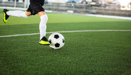 Selective focus to football with motion blur of kid soccer player shoot it on artificial turf. Soccer player training for football match.