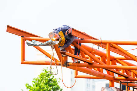 The welding workers at structures site. Worker is welding steel structures. Workers are also working at high altitude with a set of fall protection devices.