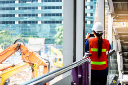 The woman foreman is standing to monitor and take photo with smartphone to control the demolition of the building. The woman worker with blurry excavator at construction site. Zdjęcie Seryjne