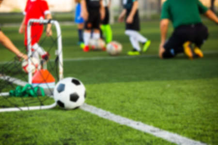 Blurry soccer ball with kid soccer player and soccer training equipment on green artificial turf. Sport background. Zdjęcie Seryjne