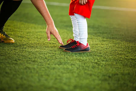 The coach is pointing the finger at the feet of a kid  soccer player to suggest playing soccer.
