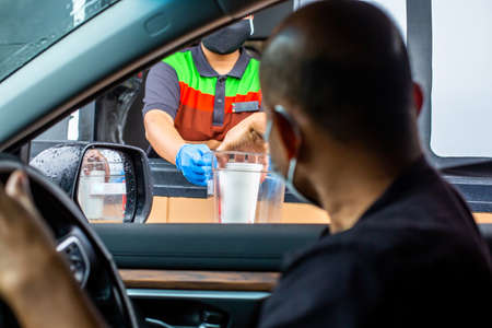 Selective focus to hand of staff wearing medical glove and mask  to handed a food to customer. Drive thru and take away concept.