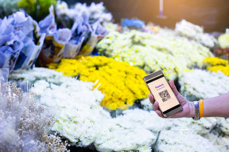 Selective focus to QR Code tag on smart phone in hand of customer with blurry many flowers in flower shop at Bangkok flower market, Thailand. Qr code payment concept.