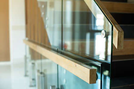 Selective focus to wooden railings mounted to glass in modern building.