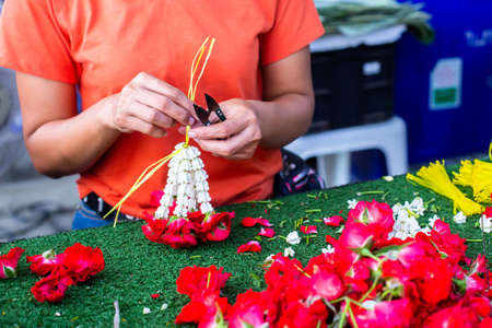 Asian woman staff is stringing flower garlands in flower shop at Bangkok flower market, Thailand.