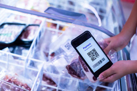 Selective focus to QR code tag on smartphone with blurry  frozen food at supermarket, Customer scanning QR Code for information product and payment online.