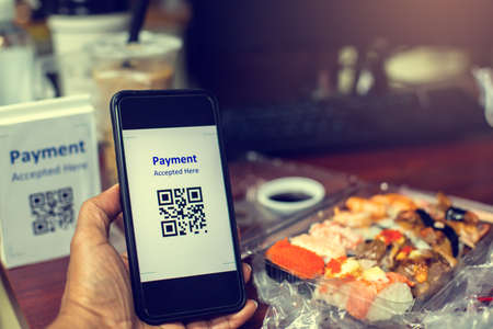 Customer hand using smart phone to scan QR code tag with blur  Sushi set or Japanese food meal on desk to accepted generate digital pay without money for food delivery payment. Qr code payment concept