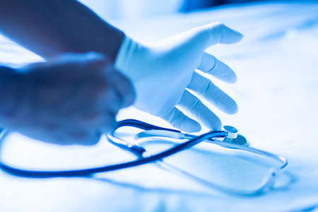 Selective focus to hands of medicine doctor wearing white  gloves and stethoscope to prepare for treatment. Healthcare and medical concept.