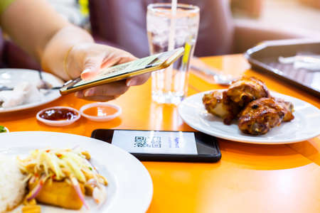 Selective focus to smartphone in hand to scan QR code on tag with blurry food, dessert and customers in restaurant to accepted generate digital pay without money. Qr code payment concept.