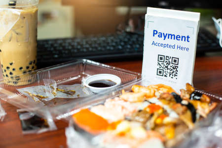 Selective focus to QR code tag with blur  Sushi set or Japanese food meal on desk for food delivery payment. Qr code payment concept.